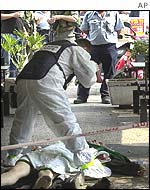 Police photograph the body of the gunman