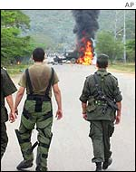 Police watch a truck blown up by the ELN