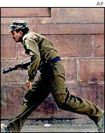 Indian policeman runs for cover during the attack on Indian parliament