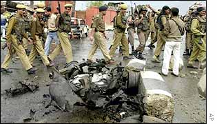 Indian policemen pass car-bomb wreck after an attack on the legislative assembly in Srinagar