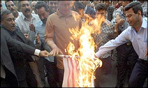 Iraqi demonstrators burn a US flag