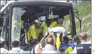 Rescue workers remove a victim from the bus