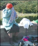 Woman pavement trader - selling her possessions