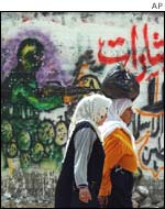 Palestinian women walk in front of graffiti support the Palestinian militant group Jihad