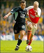 Cambridge's Shane Tudor and Blackpool's John Hills tussle for possession