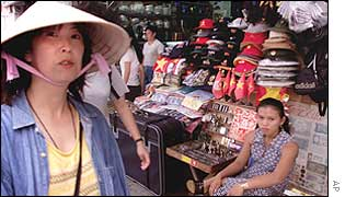 Japanese tourist walks past a vendor selling souvenirs in Ho Chi Minh city, January 2002