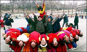 North Korean children practice a formation for a performance in the upcoming Arirang Festival, outside the Kim Il-sung stadium in Pyongyang, 26 March 2002
