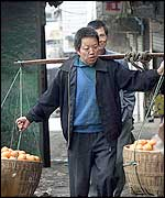Man carrying baskets of oranges