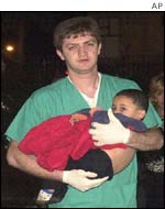 A medic carries a child victim