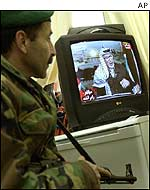 Palestinian soldier watching Arafat on TV