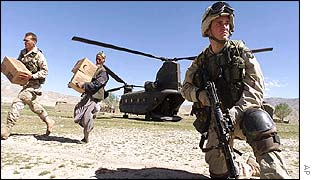 A US soldier keeps watch as US and Afghan soldiers deliver aid