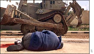 A dead Palestinian man lies in front of an Israeli armoured tank