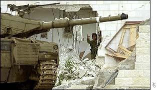 An Israeli soldier motions to a tank outside Arafat's compound