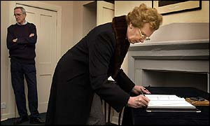 A member of the pubic signs a condolence book