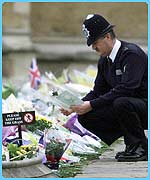 A policeman looks at flower tributes at Windsor