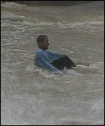 A boy struggles against the water in one of the flood channels