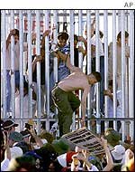 Detainee climbs through a breach in the fence at the Woomera detention centre in South Australia, 29 March 2002