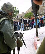 An Israeli soldier watches as activists demonstrate, near Bethlehem