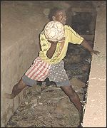A Malian boy retrieves a football from a sewer in downtown Bamako