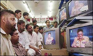 Pakistanis watch Musharraf's TV address in a shop in Karachi