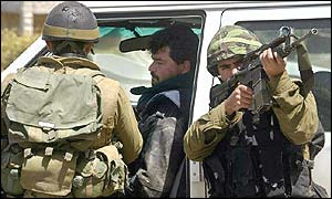Troops search a journalist's vehicle in Ramallah