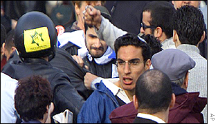 A man attempts to escape as he is hit in the face by a demonstrator
