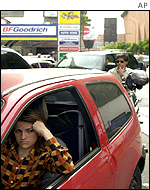 Venezuelan woman sits in her car waiting to fill it with petrol