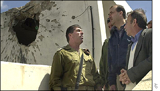 Israeli soldier speaks to Palestinians at their shell-blasted home