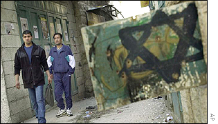 Palestinians pass a graffiti Star of David in the West Bank town of Bethlehem