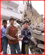 Palestinian children outside the wreckage of their home