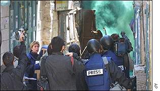 Journalists try to get a view of the fighting despite smoke grenades