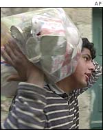 A Palestinian youth carries relief goods donated by the International Red Cross in Bethlehem