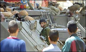 Palestinian boys stare at an Israeli soldier during a brief lifting of the curfew in Ramallah