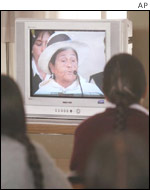 Andean women watch televised testimony of Angelica Mendoza
