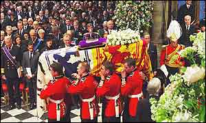 The congregation at Westminster Abbey as the Queen Mother's coffin is brought in for the service