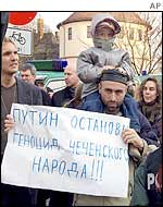 Ethnic Chechen Hampascha Irashanov, who lives in Germany, holds a poster demanding Mr Putin stop the genocide of Chechens