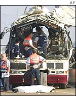 Rescue workers examine the remains of the front of the bus