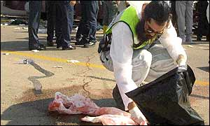 A member of the burial team mops up blood outside the bus