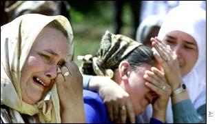 Bosnian women cry as they attend the memorial service for Srebrenica victims