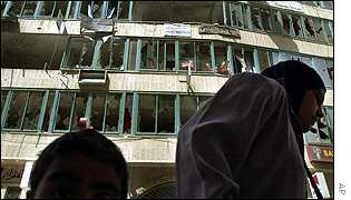 Palestinians pass shattered building in Ramallah
