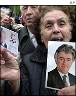 Woman holds up pictures of Radovan Karadzic and Slobodan Milosevic