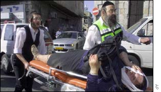 Emergency workers carry away an injured woman