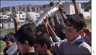 Boys play with an Israeli rocket launcher found in Jenin