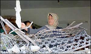 A woman examines the ruins of her home in Jenin