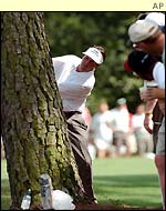 Phil Mickelson hits from behind a tree on the 8th