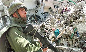 Israeli soldier stands in front of a demolished building in Jenin refugee camp