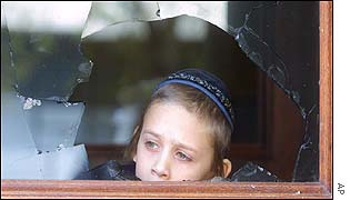 Boy peers through broken synagogue window