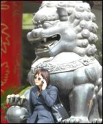 Mobile phone user seated on a statue of a lion