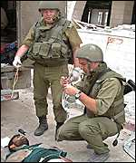 Photo released by the Israeli Defense Forces, two soldiers treat one of the wounded released from the church
