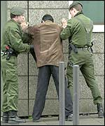 German police stop a man outside the Frankfurt court